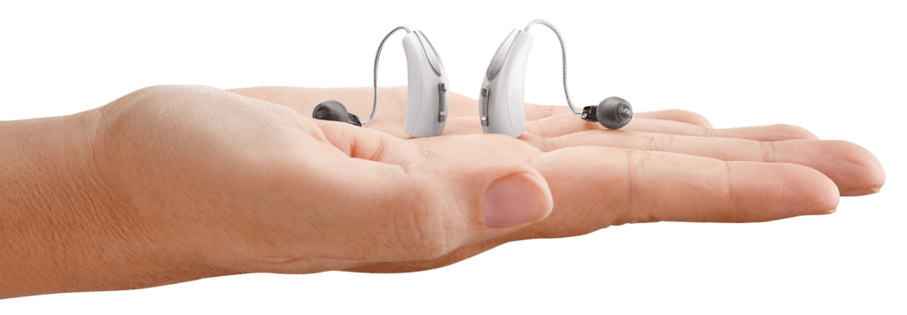 Behind-the-ear hearing aids in hand with transparent background